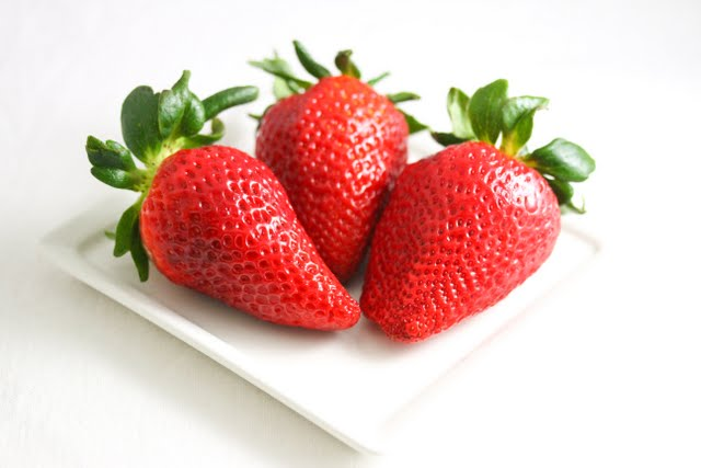 close-up photo of three strawberries on a plate