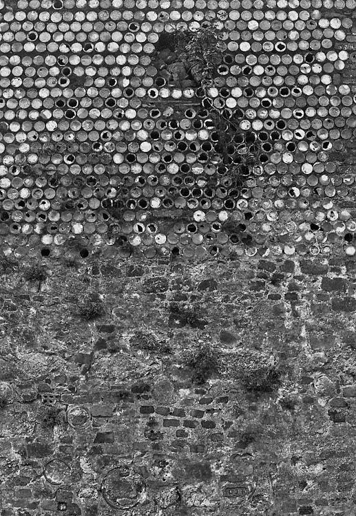 Parede com o reboco muito degradado mostrando o seu interior, composto de elementos cerâmicos também já degradados mas dando um efeito gráfico modular