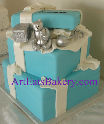 Tiffany style blue fondant presents custom creative baby shower cake design with silver toy block, rattle and teddy bear.