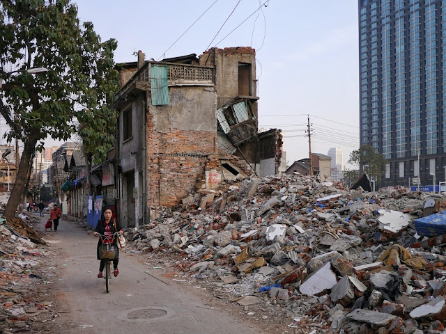 woman riding a bicycle past demolished buildings and a modern tall building in the background