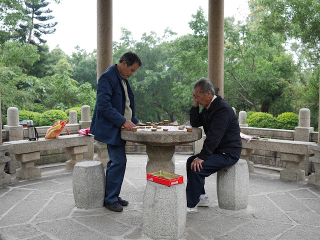 two men playing xiangqi (chinese chess) under a pagoda in Beishan Park, Yangjiang, China