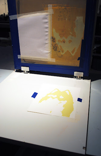 Lifting the screen to reveal the print.
