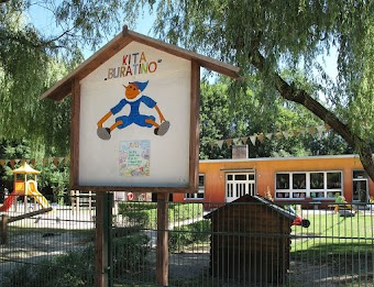 Kindertagesstätte von außen. Eingangsschild mit Pinoccio-Figur: »Kita Buratino«.