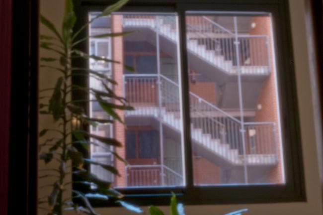 Fotografia estenopeica de una venta y al fondo una escalera de incendios