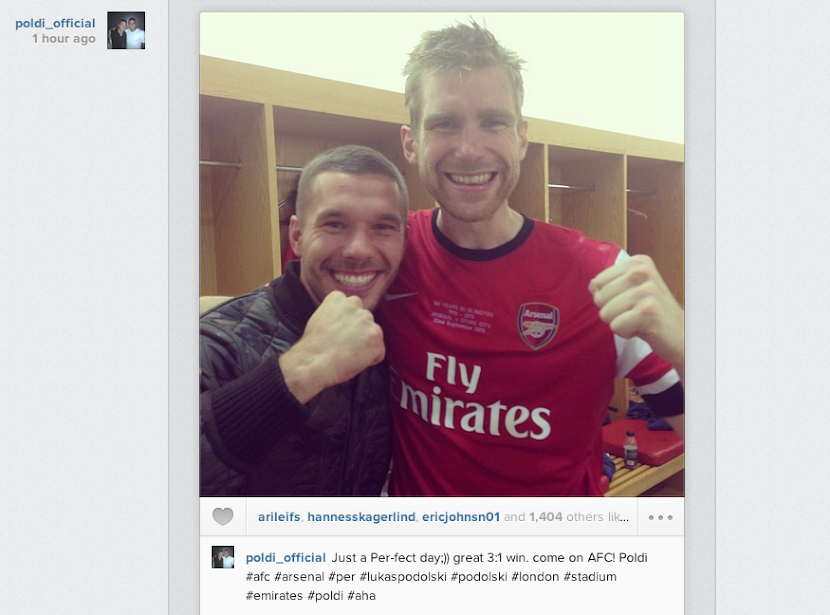 Lukas Podolski celebrates Stoke win with Per Mertesacker in Arsenal changing room