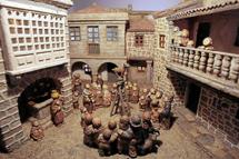 Belen de Baltar: plaza del pueblo con gente reunida en torno a una cabra en lo alto de una escalera