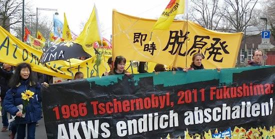 Atomkraftgegnerinnen mit Fahnen und Transparenten: »1986 Tschernobyl, 2011 Fukushima: AKWs endlich abschalten!«.
