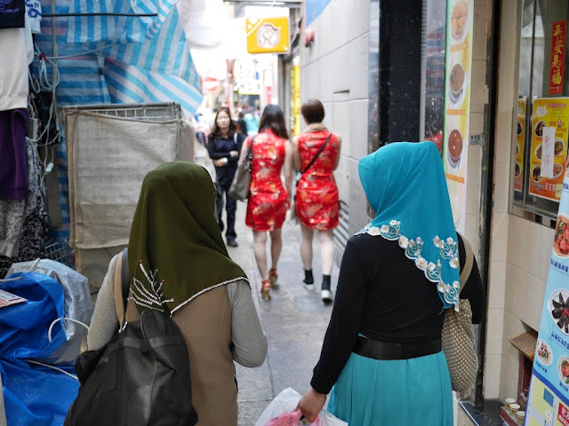 two women wearing hijabs and two other women in the distance wearing cheongsam (qipaos)