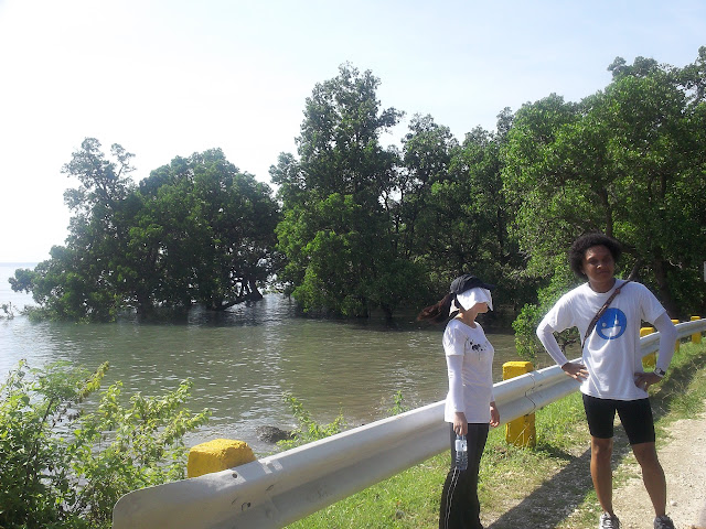 ayn and fred -- cebu runners posing with sea / mangroves at the back