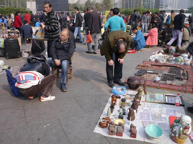 man having his shoes cleaned at an outdoor antique market in Changsha, China