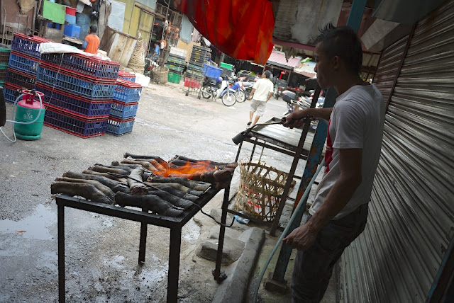 man blowtorching cow feet at Bazaar Baru Chow Kit in Kuala Lumpur, Malaysia
