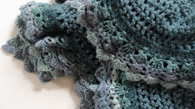 Crochet shawl, chunky wool with contrasting lace edge. Colours go from dark aqua to light aqua through different shades of blue