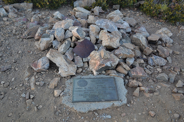 metal rectangle with words beside a rock pile with a shovel head