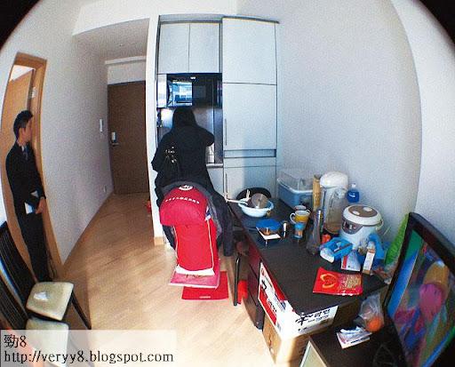 正放盤出租的 D室,廳內放下一張摺枱、一個電視機櫃及兩張座椅,已佔去大部分空間,大門前的長走廊反而是全屋最寬敞的。(廖健昌攝)
