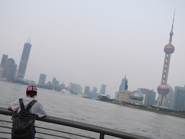 "young woman wearing a ""BOSS"" cap leaning against a railing next to the Huangpu River in Shanghai with the Oriental Pearl Tower in the background"