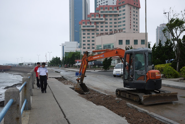 excavator digging up portion the sidewalk as people walk by