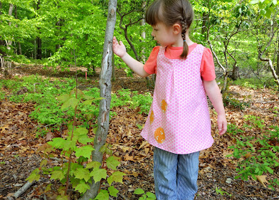 Made with Moxie:Roly-Poly Pinafore pattern review. Girl wearing Roly-Poly Pinafore walking in the woods.