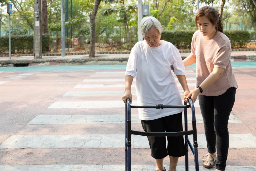Menina auxiliando senhora com andador a se locomover