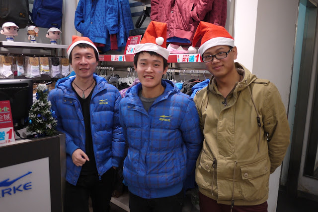 Three young men wearing Santa hats in Putian, China