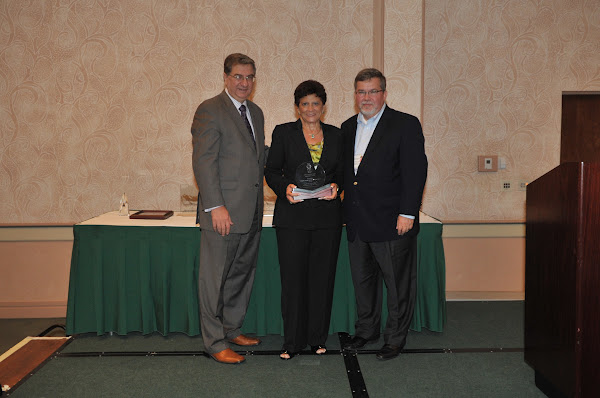Luz Puello, Project Coodinator for Catholic Health Services of Long Island, accepts the 2011 Community Health Improvement Award from HANYS President Daniel Sisto (left) and Joseph McDonald, President and Chief Executive Officer of Catholic Health System (right).