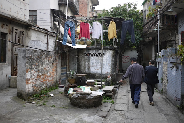 two men walking underneath hanging laundry in Guangzhou alley