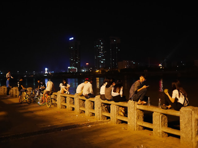people sitting on a stone railing next to the Xiang River at night