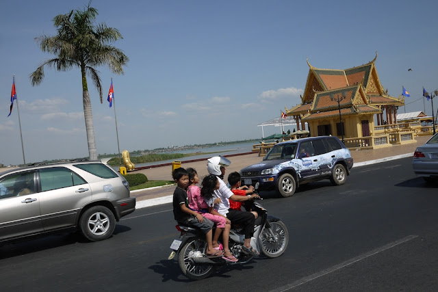 man with four children on a motorbike
