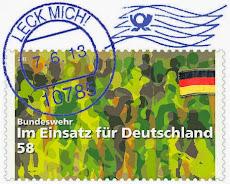 Briefmarke. Menschen in Tarnfarben. Fahne schwarz-rot-gold: »Bundeswehr. Im Einsatz für Deutschland«, Poststempel: »Leck mich! 7.6.13«.