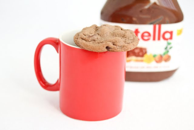 photo of a cookie on top of a mug