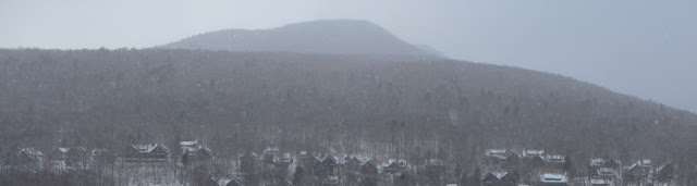 cottages on a mountainside in a snowstorm, with another mountain in the distance