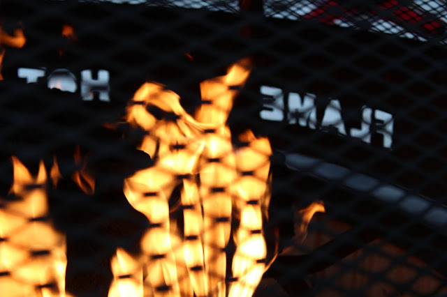 flames leaping in a firepit, with the words 'flame' and 'hot' cut in the side of the metal grate