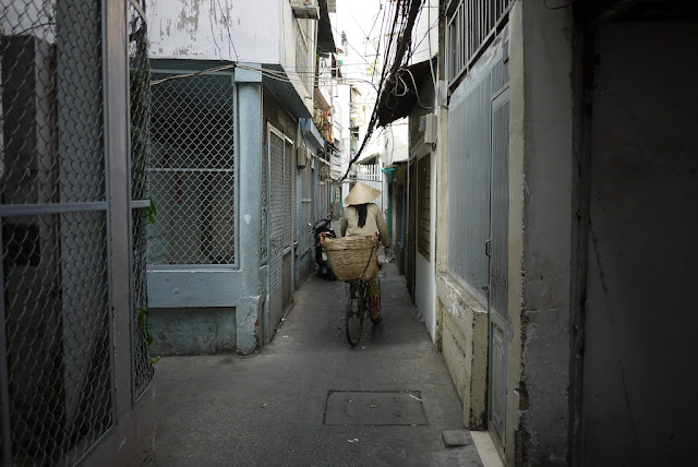 woman wearing a nón lá (leaf hat) and riding a bicycle through a narrow alley