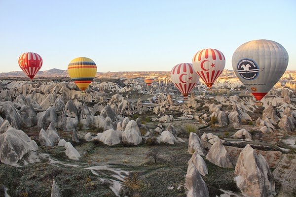 hot air balloons hovering over the massive cappadocia terrain