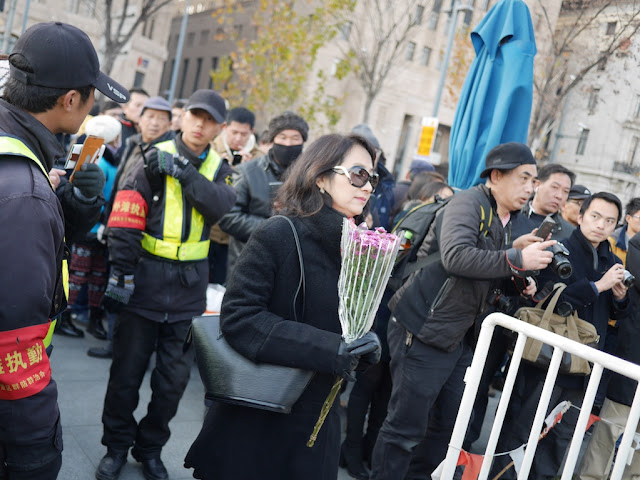 woman bringing flowers to a memorial for people killed and injured by the New Year's Eve stampede in Shanghai