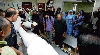ahli keluarga menguruskan jenazah Allahyarham Mustaghni di rumah mayat HTAR, semalam