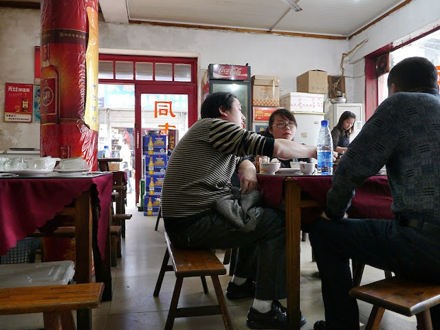 three people sitting on benches eating lunch in Changsha, China