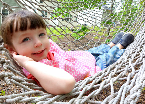 Made with Moxie:Roly-Poly Pinafore pattern review. Smiling girl laying in hammock with arms behind her head.