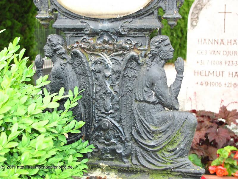Engel auf dem unteren Teil eines eisernen Grabkreuzes.