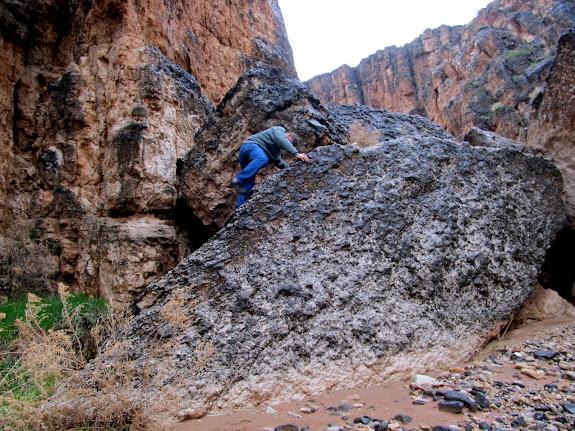 Paul climbing backward down a difficult boulder