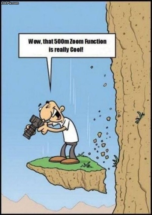 cartoon of a guy falling down a cliff while looking through his camera...boy, that zoom lens works great