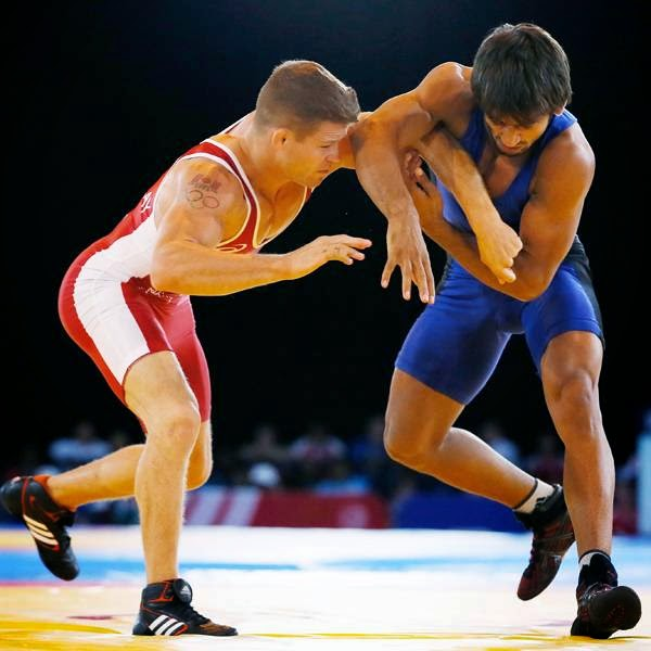 David Tremblay, left, of Canada wrestles Bajrang of India in their men's 61 kg gold medal wrestling bout at the Commonwealth Games Glasgow 2014, in Glasgow, on July 30, 2014.