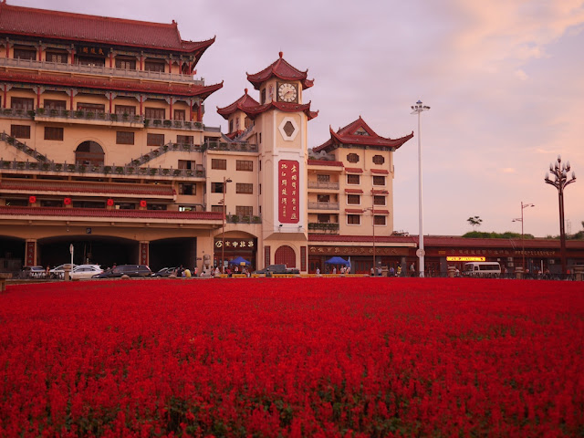 field of red flowers in front if Chinese style gate building