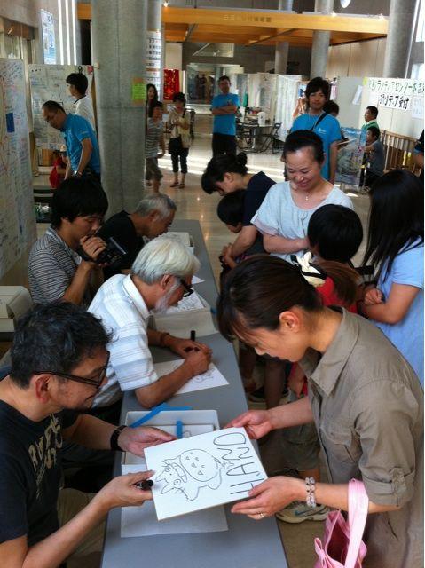 2011年7月2日と3日、東日本大震災の被災地を訪れサイン会をする宮崎駿監督と庵野秀明監督