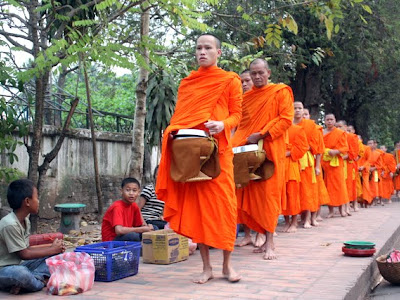 Monks collecting alms on their daily procession in Luang Prabang Laos