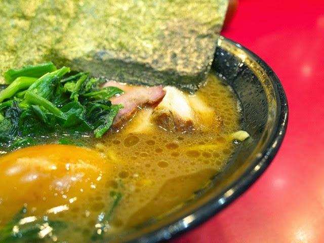 鶏油が浮いた、褐色のラーメンスープの表面
