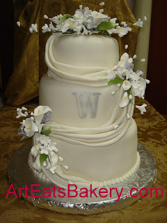 Three tier fondant draped wedding cake with silver monogram and elegant sugar flowers