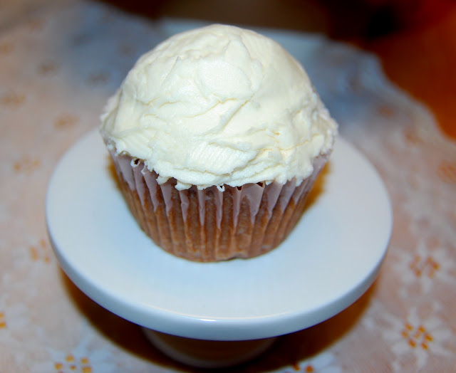 A single vegan Irish cream cupcake on a cake stand.