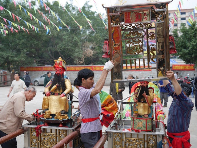 people taking the enclosures off god figures in Maoming, China