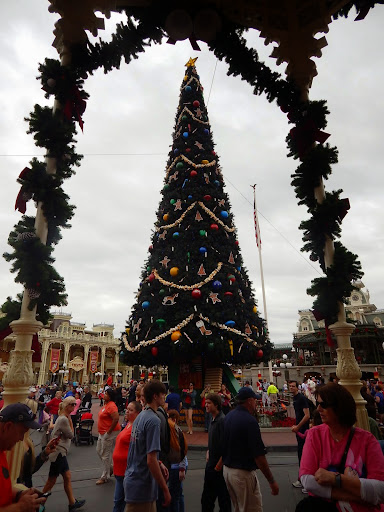 Celebrating Christmas at Disney -  giant tree surrounded by toy soldiers taking center stage just past the Magic Kingdom entrance.