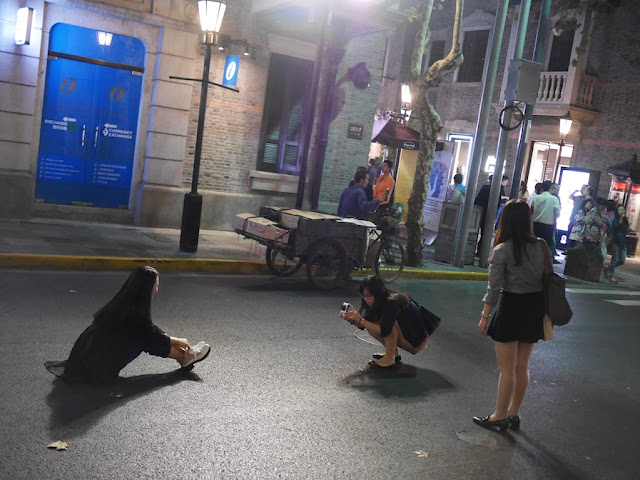 young woman being photographed while sitting in the middle of a street at night